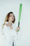 Pretty sexy woman with long hair holds green baseball bat Royalty Free Stock Image