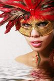 Pretty woman in mask - water effect. Beautiful woman in mask with red feathers in water - spa