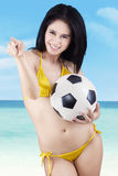 Pretty sexy woman with a soccer ball. Portrait of sexy woman wearing bikini holding a soccer ball pointing at camera Royalty Free Stock Images