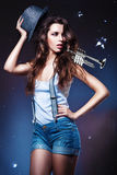Pretty sexy woman with suspenders in hat and horn Royalty Free Stock Photography