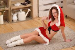 Pretty sexy woman wearing Santa Claus clothes, sitting on a warm rug Stock Photo