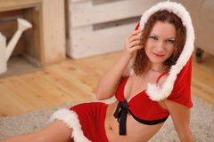 Pretty sexy woman wearing Santa Claus clothes, sitting on a warm rug. Pretty sexy woman wearing Santa Claus clothes, sitting on warm rug Stock Photography