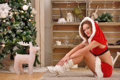 Pretty sexy woman wearing Santa Claus clothes, sitting on a warm rug. Pretty sexy woman wearing Santa Claus clothes, sitting on warm rug Royalty Free Stock Images