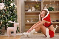 Pretty sexy woman wearing Santa Claus clothes, sitting on a warm rug Royalty Free Stock Photo