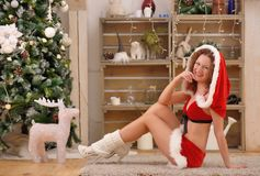Pretty sexy woman wearing Santa Claus clothes, sitting on a warm rug Stock Images