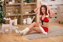 Pretty sexy woman wearing Santa Claus clothes, sitting on a warm rug Royalty Free Stock Photography