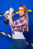 Pretty sexy worker girl in chechered shirt, build goggles and je. Isolated on blue, attractive sexy brunette caucasian builder girl in chechered shirt, yellow Stock Images