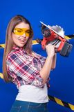 Pretty sexy worker girl in chechered shirt, build goggles and je. Isolated on blue, attractive sexy brunette caucasian builder girl in chechered shirt, yellow Royalty Free Stock Photography