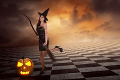 Pretty sexy young asian witch woman with a broom Stock Image