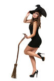 Pretty young brunette witch with a broom Stock Image