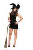 Pretty sexy young brunette witch with a broom Royalty Free Stock Photos