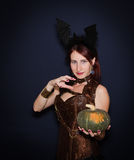 Pretty sexy young witch with a pumpkin, Halloween. Royalty Free Stock Photography