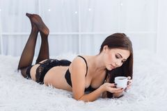 Pretty young girl in black lace underwear posing on the camera. Beauty concept. Pretty sexy young woman laying on the bed with couple of coffee in a black lace