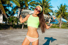 Pretty young woman stand with longboard in front of palms in sunny weather. Smiling female. Leisure.