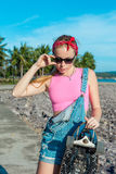 Pretty sexy young woman stand with longboard in front of sea and palms in sunny weather. Female doing active sport in Royalty Free Stock Photo