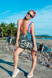 Pretty sexy young woman stand with longboard in front of sea and palms in sunny weather. Female doing active sport in Royalty Free Stock Photography