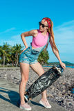 Pretty sexy young woman stand with longboard in front of sea and palms in sunny weather. Female doing active sport in Royalty Free Stock Images