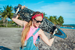 Pretty young woman stand with longboard in front of sea and palms in sunny weather. Funny smiling female. Leisure. Stock Photos
