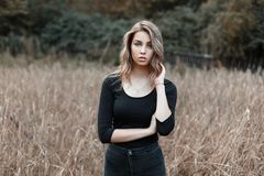 Pretty sexy young woman in vintage black shirt in fashionable jeans posing in a field among autumn dry grass. Attractive girl stock photography