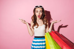 Pretty shocked girl holding shopping bags and mobile phone Stock Photo