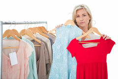 Pretty shopping blonde choosing a dress Royalty Free Stock Photos