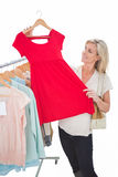 Pretty shopping blonde looking at dress Royalty Free Stock Photography