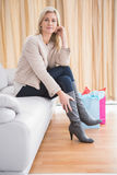 Pretty shopping blonde sitting on couch Stock Photo