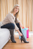 Pretty shopping blonde sitting on couch Stock Images