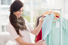 Pretty shopping brunette looking at blue dress Royalty Free Stock Photo