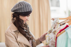 Pretty shopping brunette looking at dress Royalty Free Stock Photography