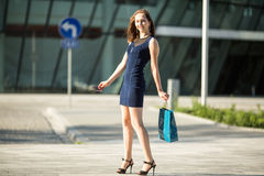 Pretty shopping-lady in the street with package. Stock Photography