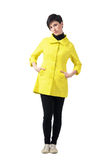 Pretty short hair brunette in yellow coat posing with hands in pockets Stock Images