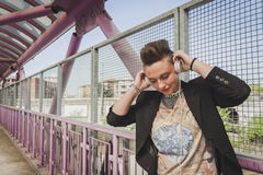 Pretty short hair girl listening to music on a bridge Stock Photos