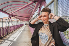 Pretty short hair girl listening to music on a bridge Stock Photos