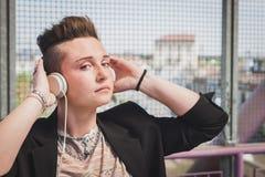 Pretty short hair girl listening to music on a bridge Stock Photography