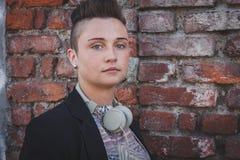 Pretty short hair girl posing against a brick wall Stock Image