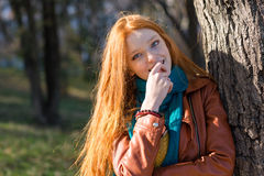 Pretty shy woman standing near the tree in park Royalty Free Stock Images