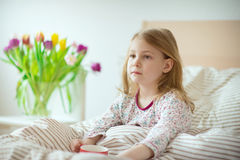 Pretty sick little child girl laying in bed drink tea royalty free stock photos