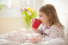 Pretty sick little child girl laying in bed drink tea. Pretty sick little child girl laying in bed and drink tea royalty free stock photo
