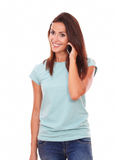 Pretty single woman talking on her mobile. Portrait of pretty single woman on blue t-shirt talking on her mobile while smiling and standing on isolated white royalty free stock photography