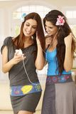 Pretty sisters listening to music on mp3 player Royalty Free Stock Photos