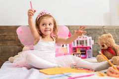 Pretty sisters playing in bedroom. Happy little fairy is holding felt pen and waving it as magic wand. She is sitting on bed and smiling. Girl is wearing pink Stock Images