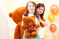 Pretty sisters posing with teddy bears in playroom Stock Photos