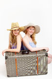 Pretty sisters traveling with a shared suitcase Royalty Free Stock Photos
