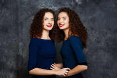 Pretty sisters twins smiling looking at camera over grey background. Royalty Free Stock Photos
