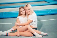 Pretty siters girls having fun indoor. Jumping on trampoline in children zone stock photos