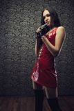 Pretty slave. Gothic girl in latex red dress standing in empty dark room royalty free stock image