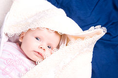 Pretty sleepy baby under a blanket. Looking at camera Stock Photo