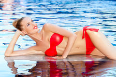 Pretty slender blonde girl reclining by a pool Royalty Free Stock Photography