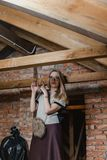 Beautiful blonde in glasses and boots standing in attic stock image